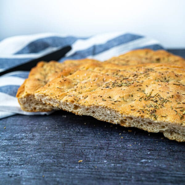 Crispy Rosemary Foccacia Cut on Board with Towel