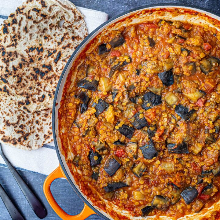 Aubergine and Red Lentil curry with naan bread in orange pan