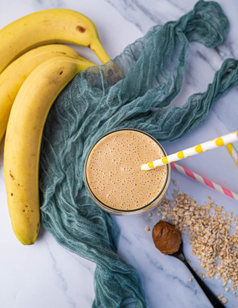 Biscoff smoothie with oats and banana in glass with yellow straw, view from top