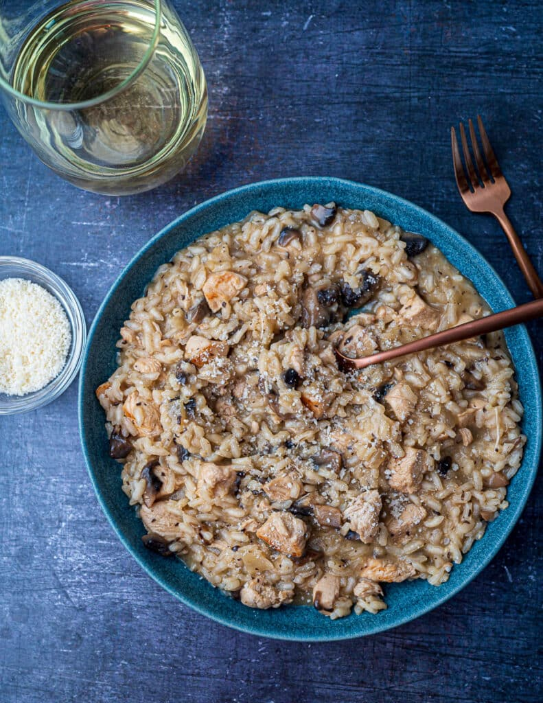Creamy chicken risotto in bowl with spoon in