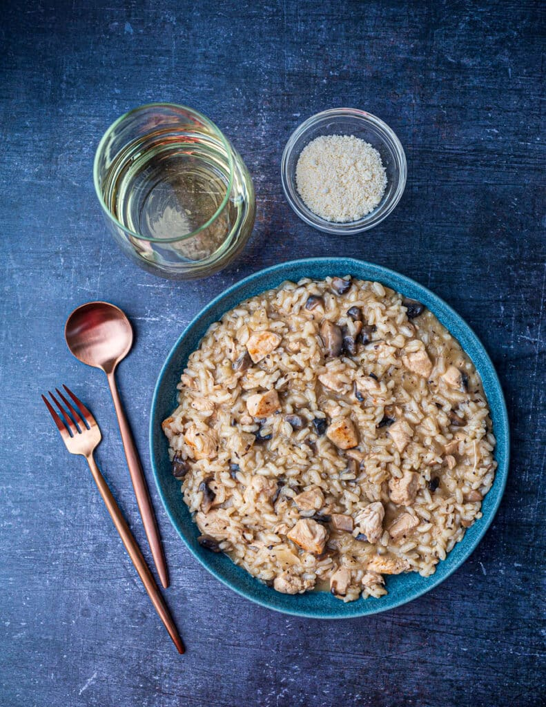Creamy chicken risotto in bowl with cutlery, glass of white wine and Parmesan