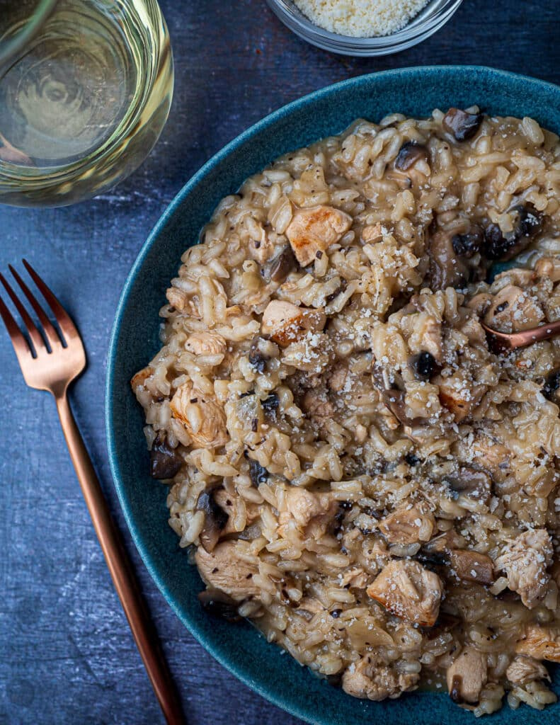Creamy chicken risotto in bowl with fork and glass of white wine