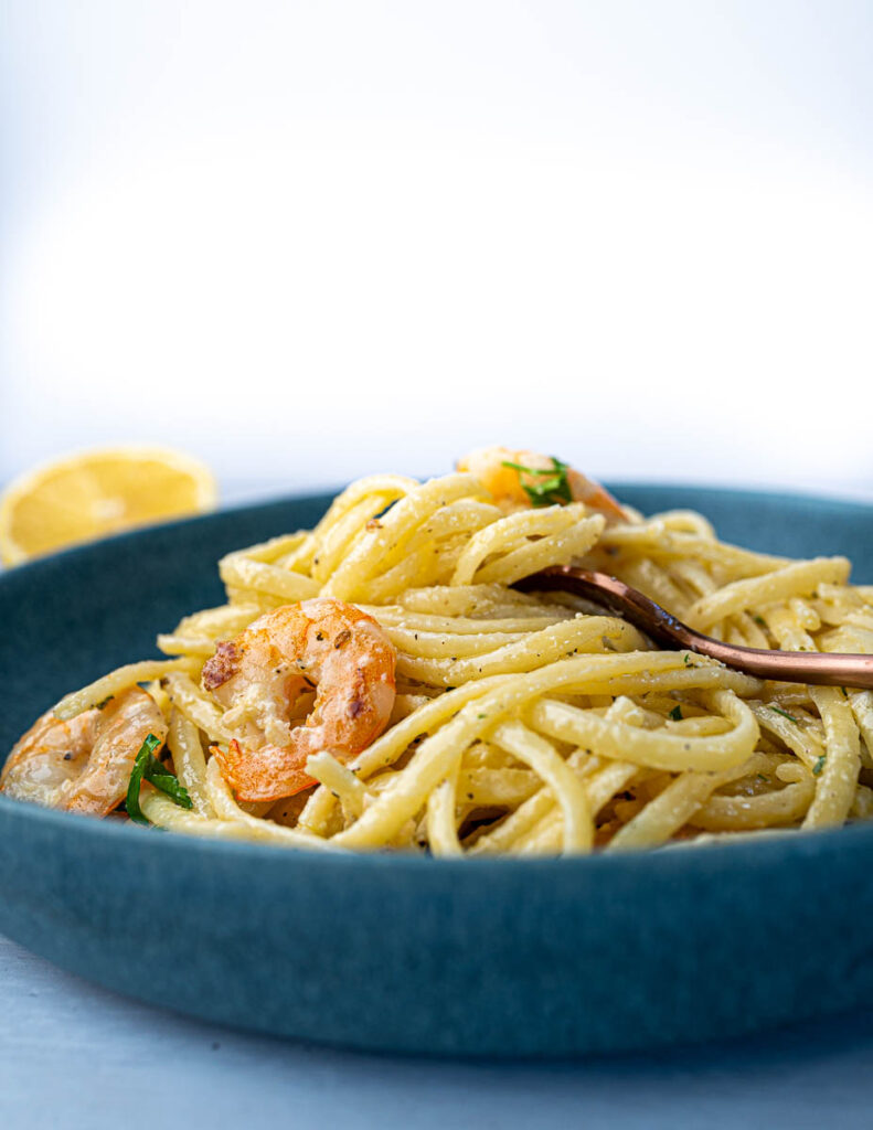 Creamy Prawn Linguine in pan with lemon with fork in bowl