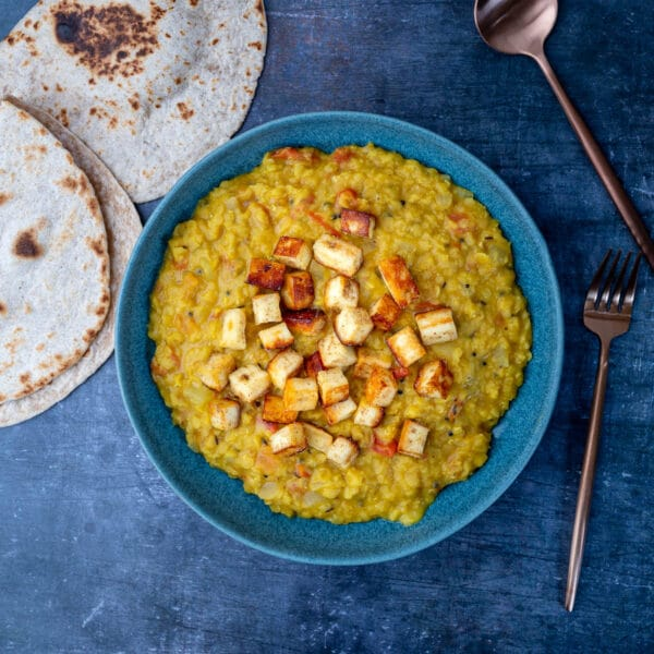Red lentil curry with spicy panner in bowl with roti