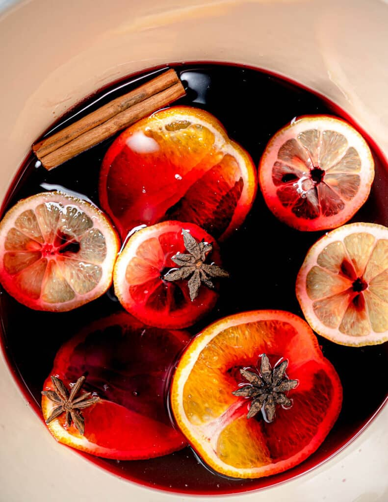 Close up of mulled wine with lemon, orange, and cinnamon sticks in saucepan