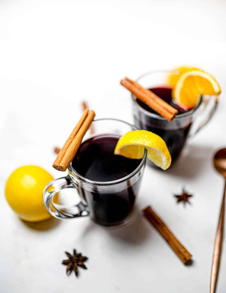Two glasses of mulled wine on white table with lemon and cinnamon sticks