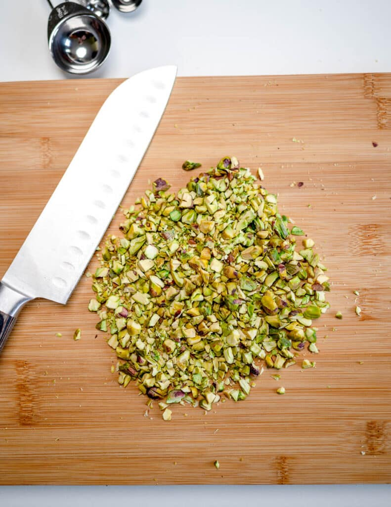 A photo of chopped pistachios on chopping board with a knife