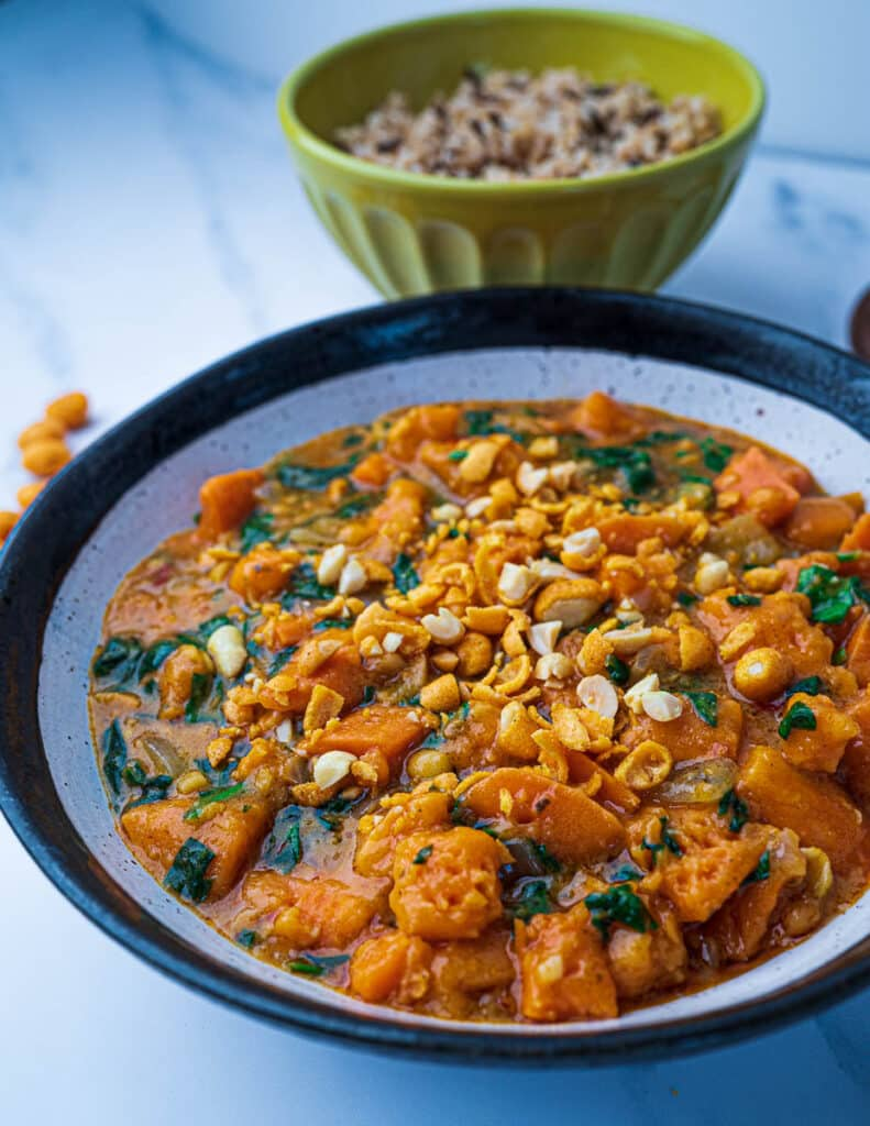 Close up of Thai red curry in bowl with peanuts on top