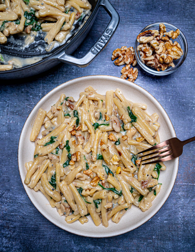 Photo of a plate of gorgonzola and walnut pasta with fork and small bowl with walnuts on the side