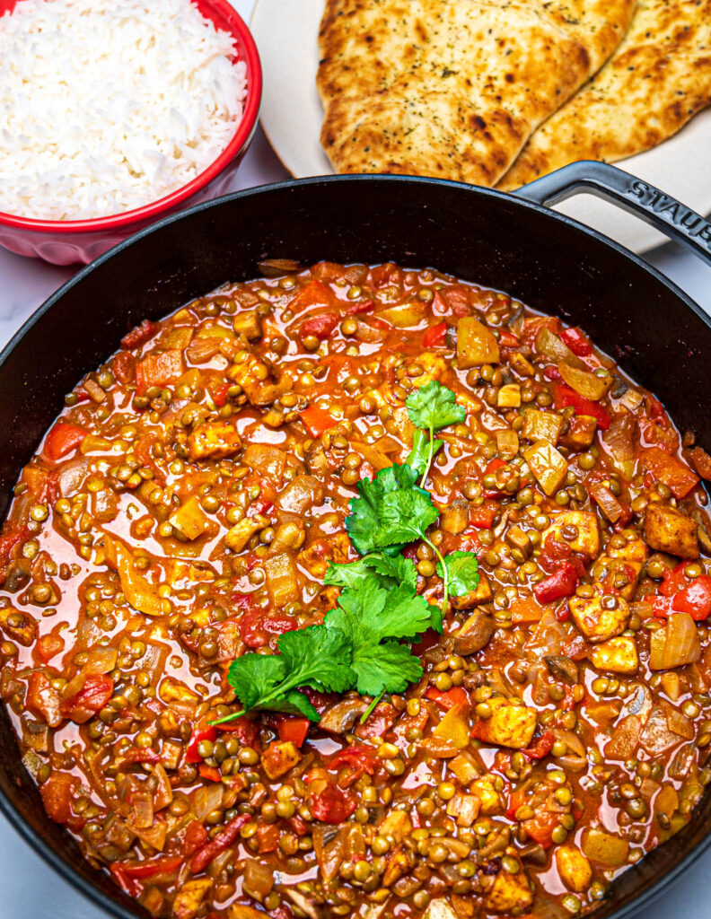 Closeup photo of a pan with green lentil and halloumi curry with rice and naan bread on the side