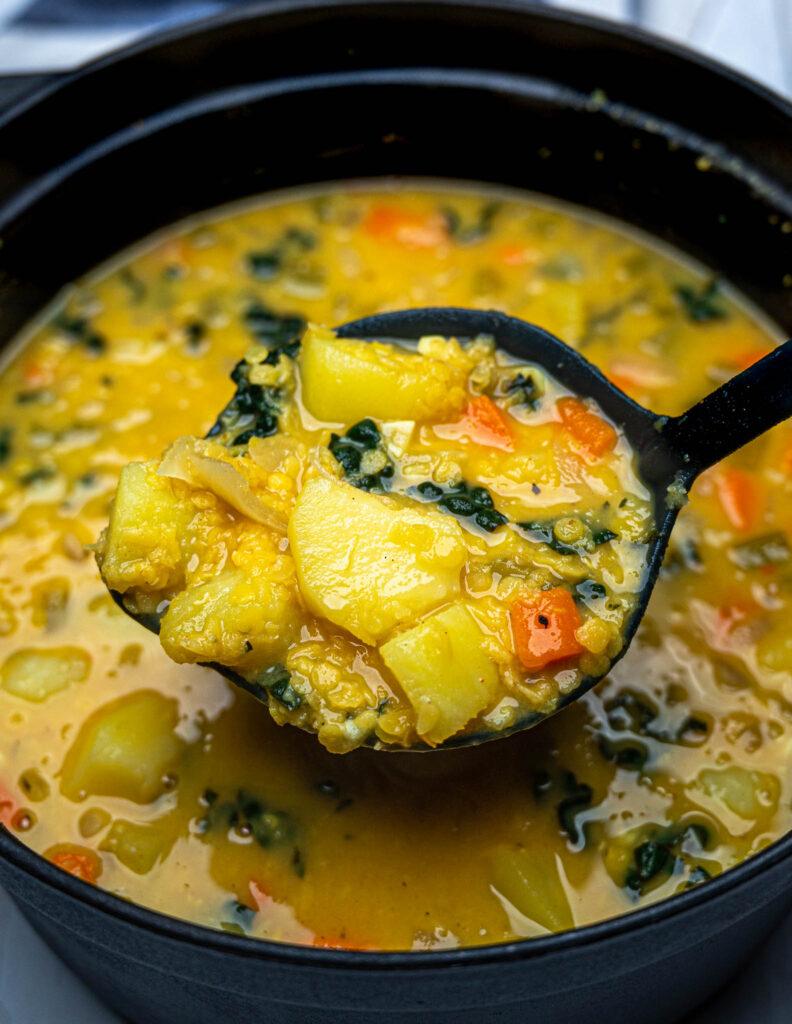 Close up of a ladle of red lentil potato soup over a black pot