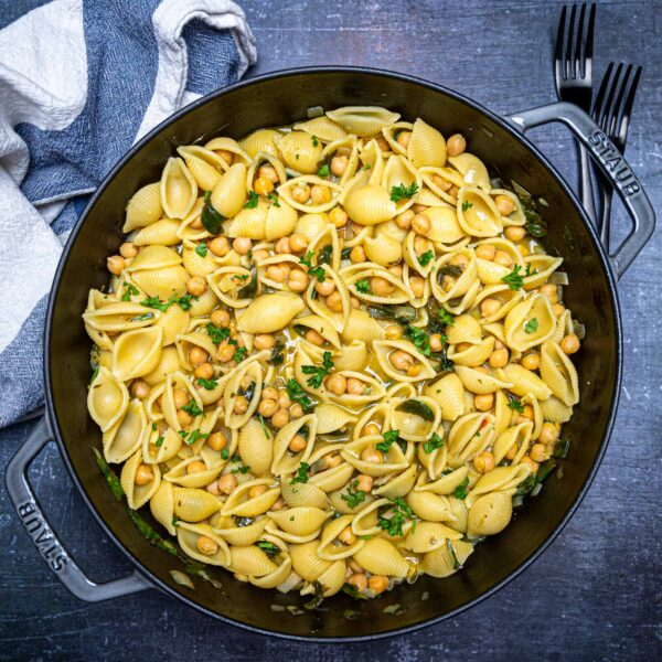 A large pan with chermoula pasta with chickpeas and spinach