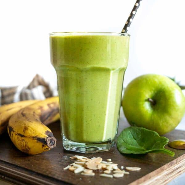 A glass of green smoothie surrounded by bananas, apples, and almond flakes