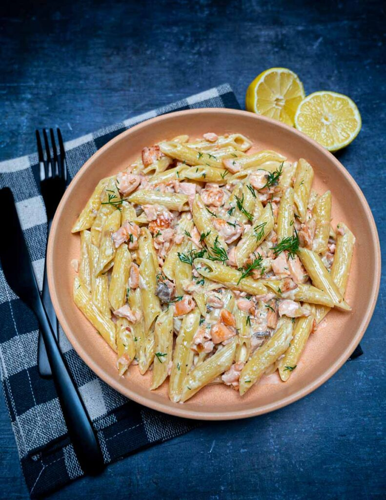An orange bowl with salmon pasta and lemons on the side