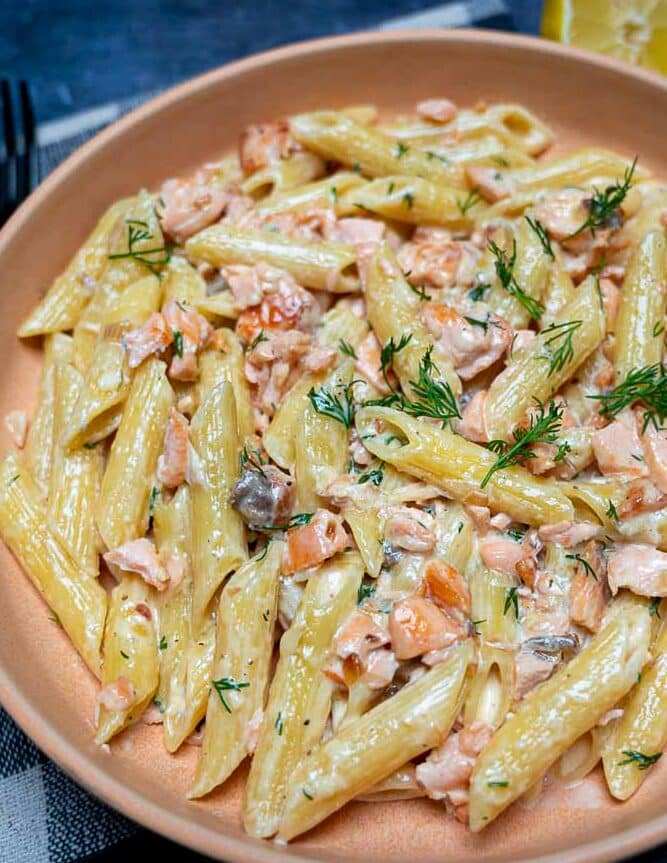 Close up of an orange bowl with salmon pasta and lemons on the side
