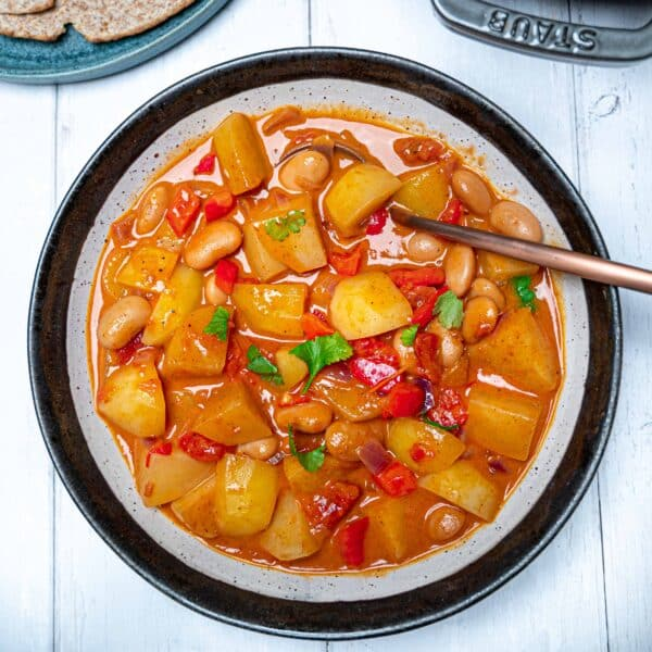 A bowl of vegan potato curry with butter beans and red peppers