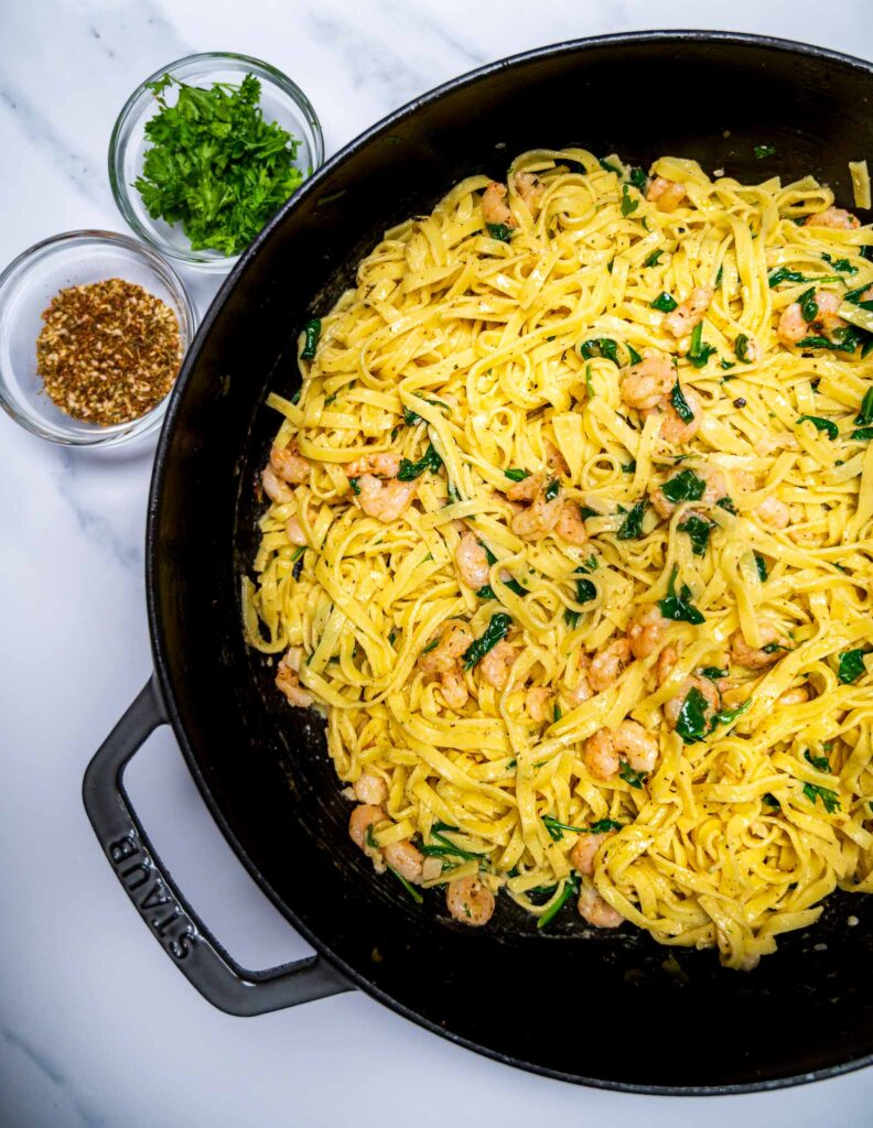 Close up of a pot of pasta with shrimp and spinach with small bowls of zaatar and parsley