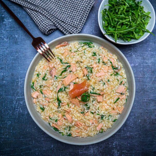 A bowl os risotto with salmon and a smaller bowl of rocket salad