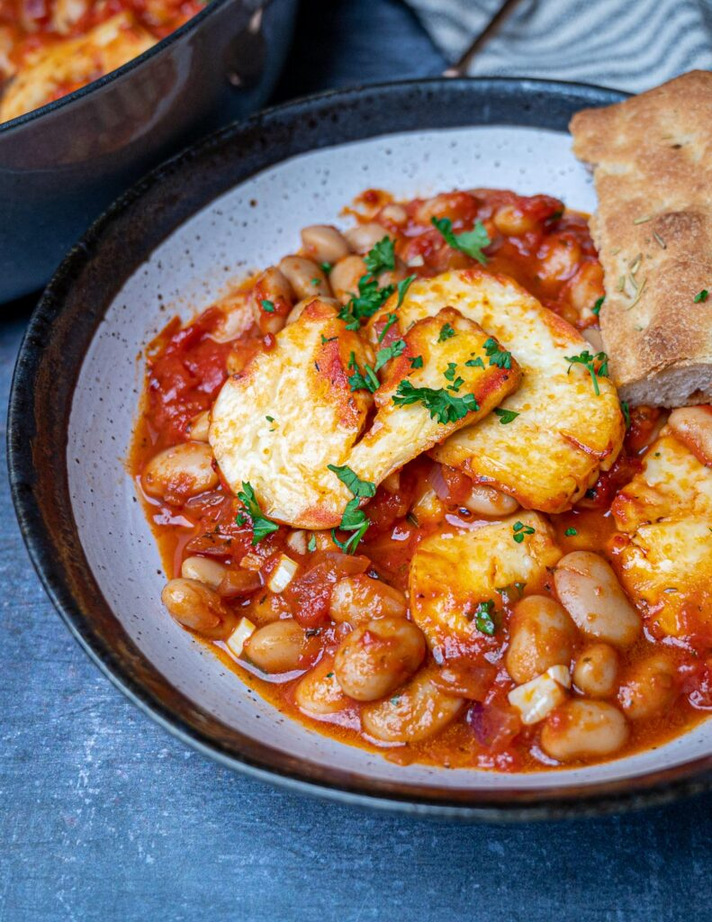 A photo of a bowl with baked beans and halloumi