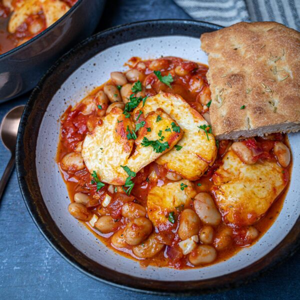A close up of a bowl with baked beans and halloumi