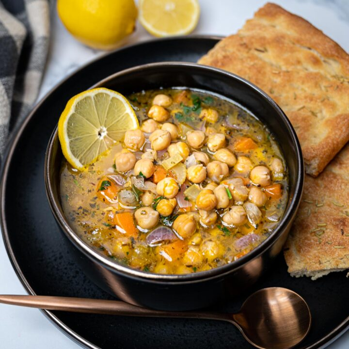 Photo of a black bowl of chickpea soup with lemon