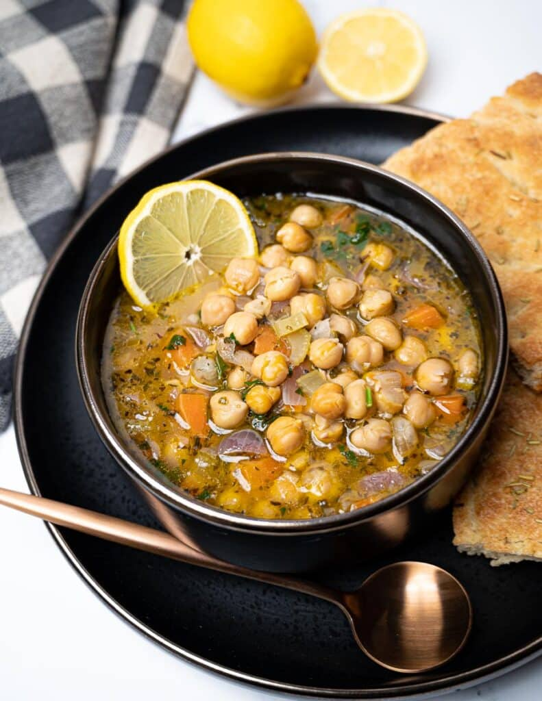 A bowl of chickpea soup with lemon and a slice of bread