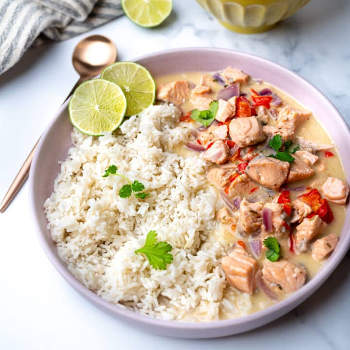 A pink bowl with salmon curry and jasmine rice