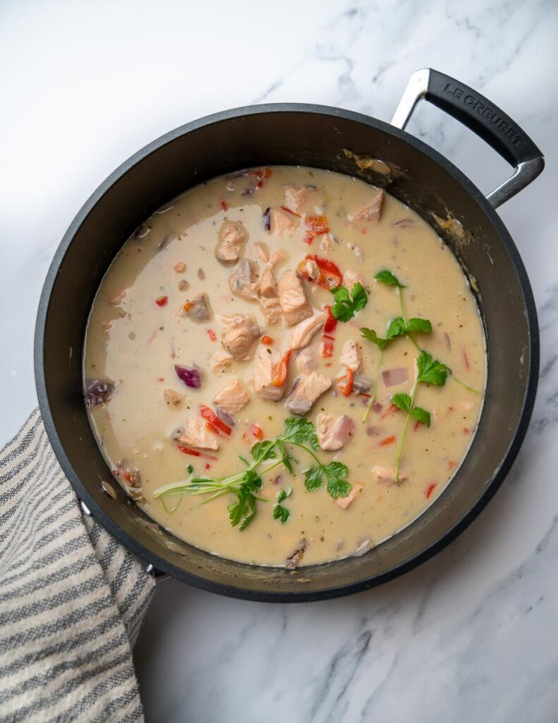 A pan with salmon green Thai curry