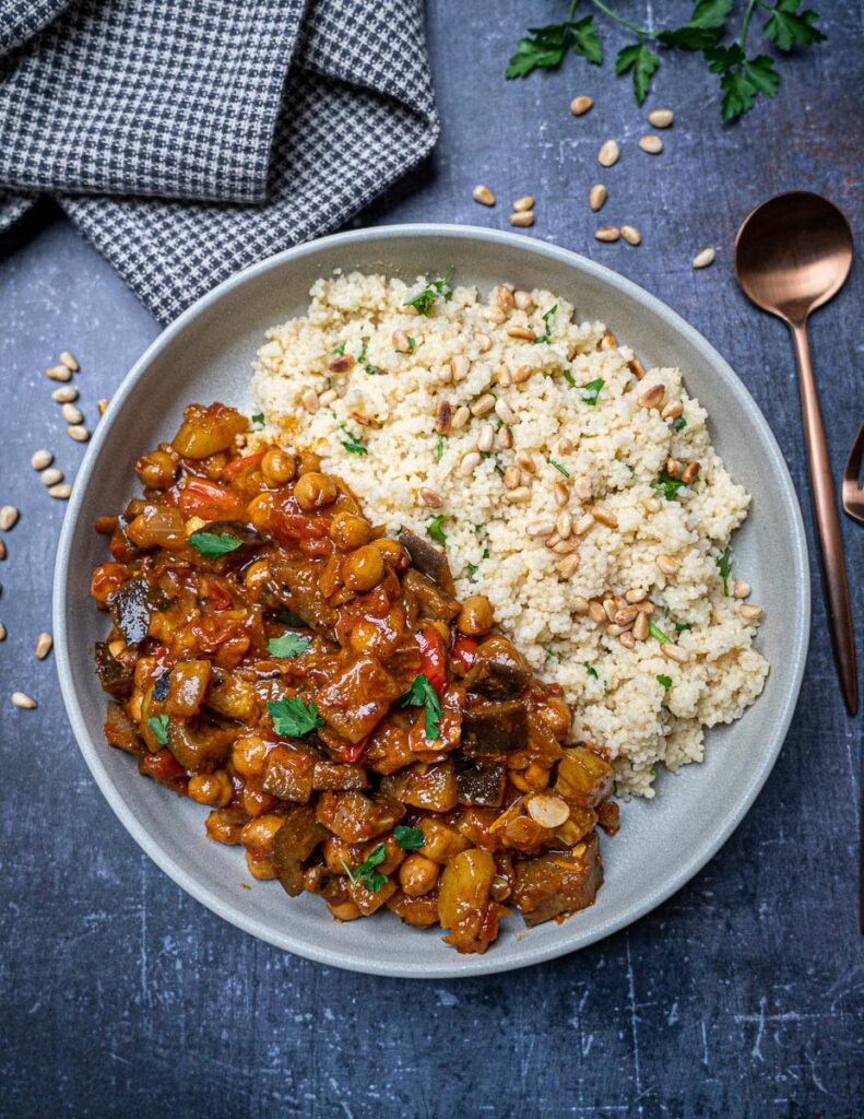 A bowl of vegan aubergine tagine with couscous on the side