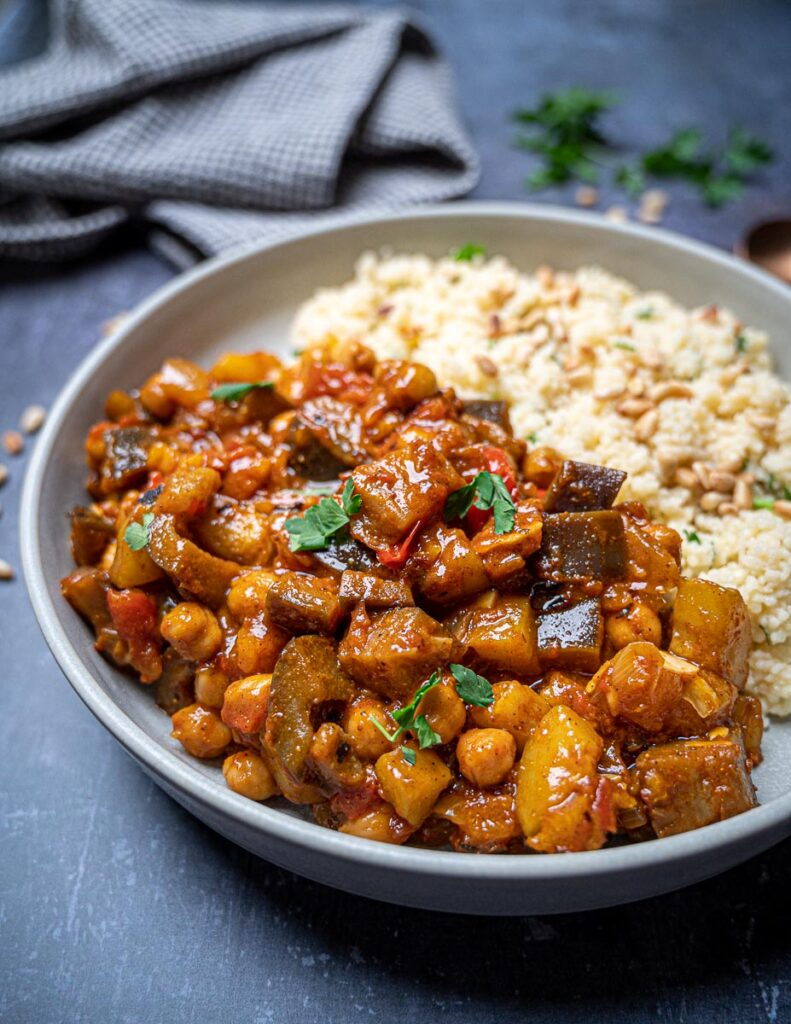 Close up photo of a bowl of vegan aubergine tagine with couscous