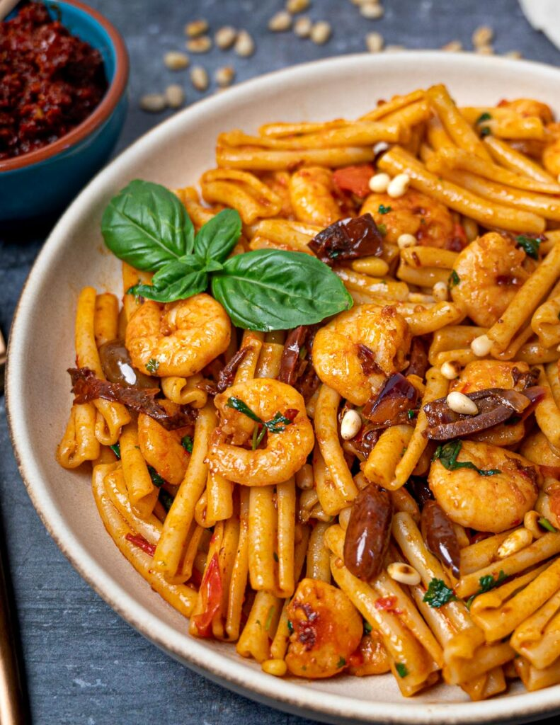 A plate of harissa pasta with prawns