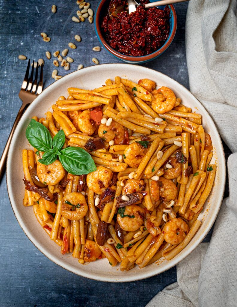 A photo of pasta with a bowl of rose harissa on the side