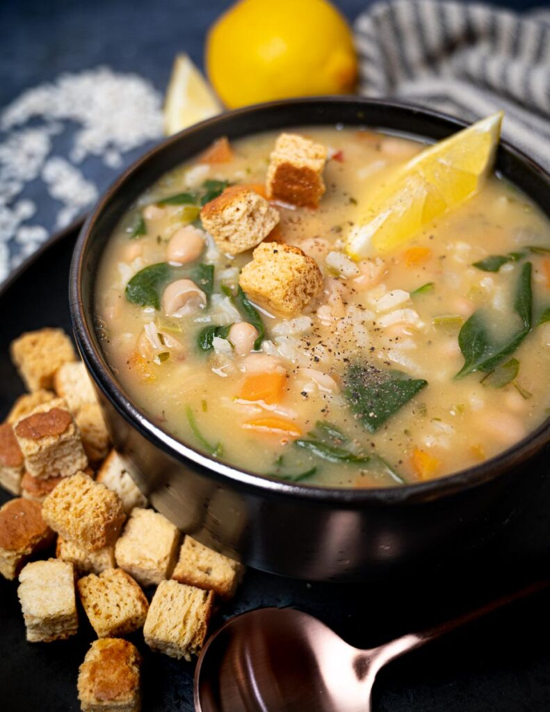 A photo of vegan soup with croutons and lemon