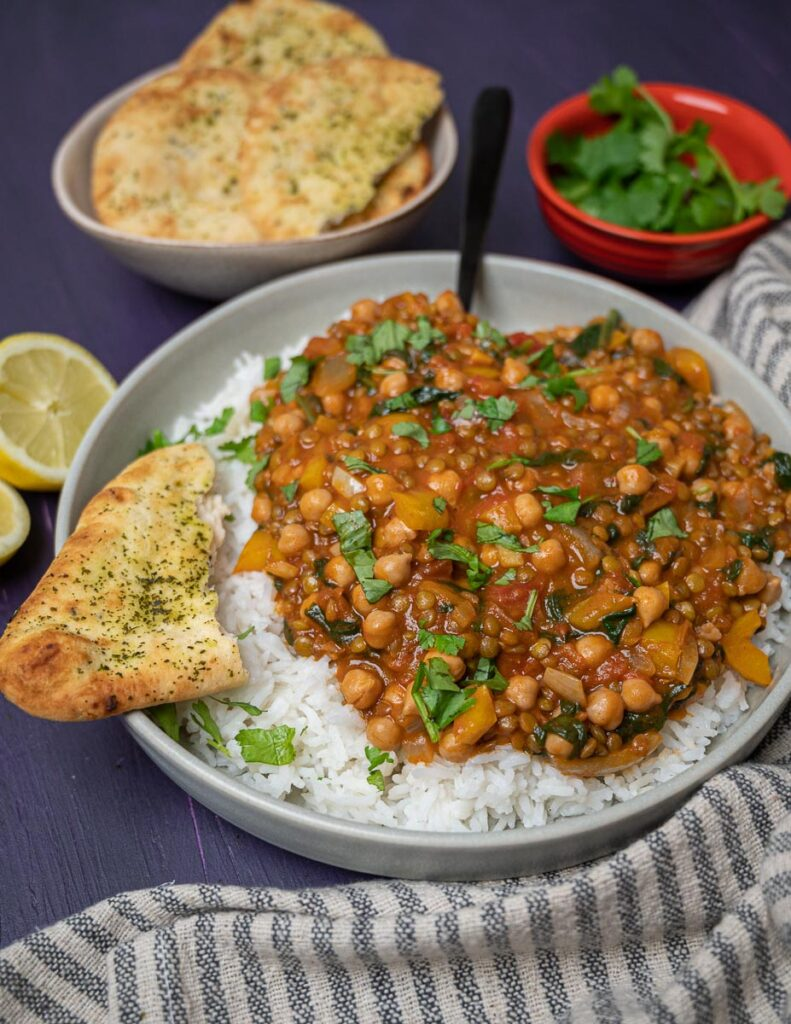 Photo of a bowl of chickpea and lentil curry with naan bread and rice