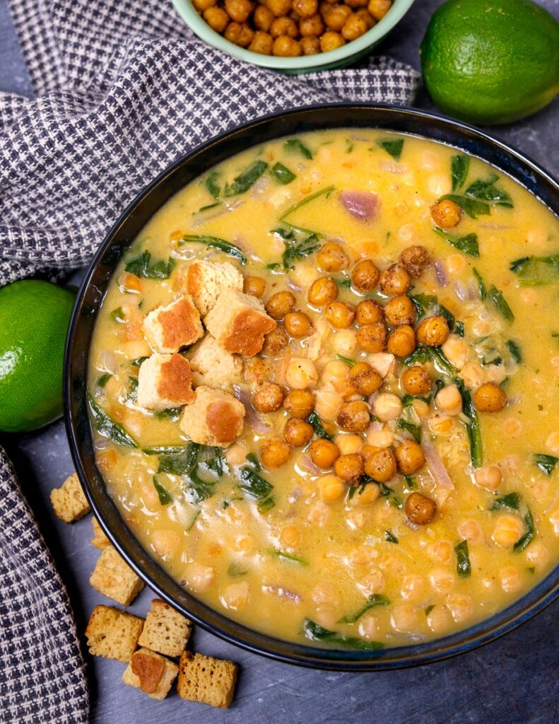 A photo of a bowl of chickpea and coconut soup with a lime and croutons on the side