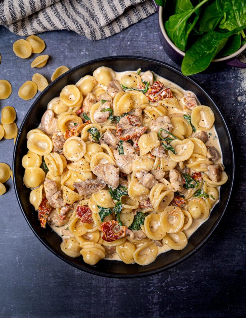 A photo of a bowl of chicken pasta with sundried toamtoes