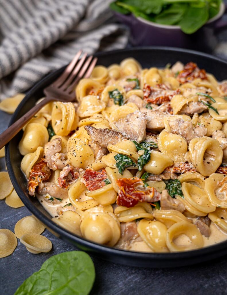 A close-up photo of a bowl of Tuscan chicken pasta