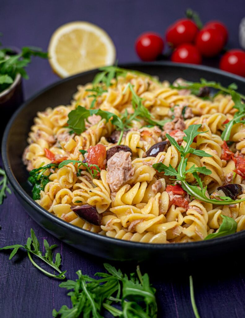 A close up photo of a bow lf pasta with cherry tomatoes and lemon on the side