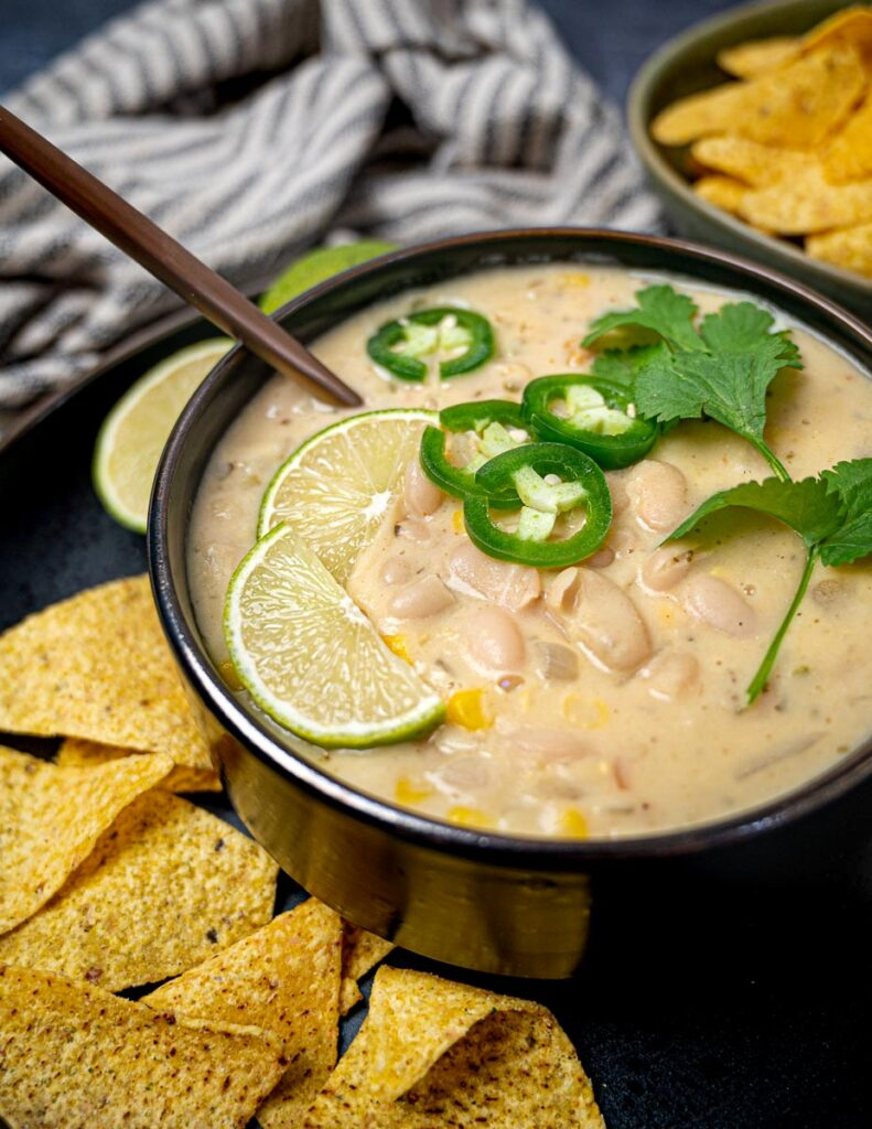 Bowl of white soup with beans, lime, and tortilla chips