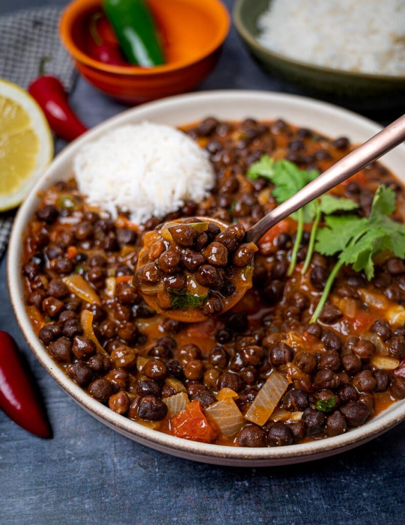 Photo of a bowl of kala chana masala with a spoonful over it