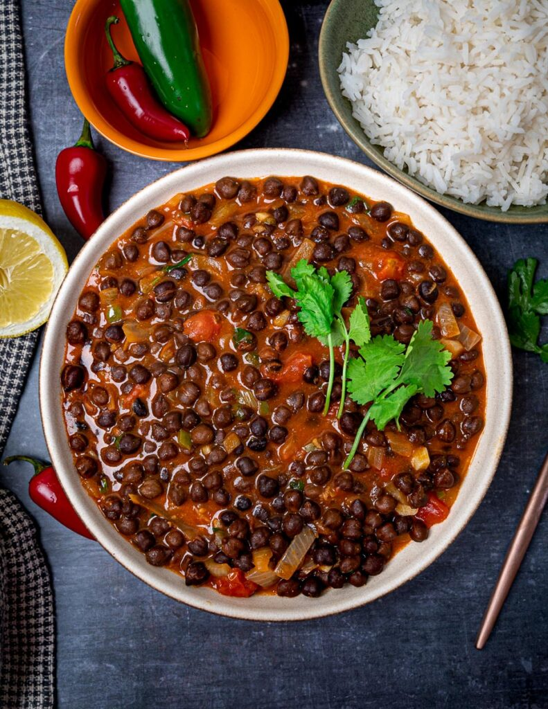 A photo of a black chickpea curry with rice on the side