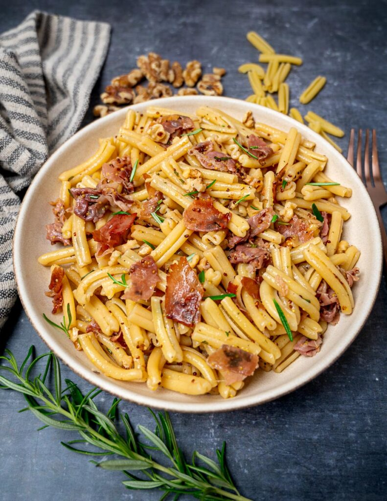 A bowl of pasta with prosciutto and a rosemary sprig on the side