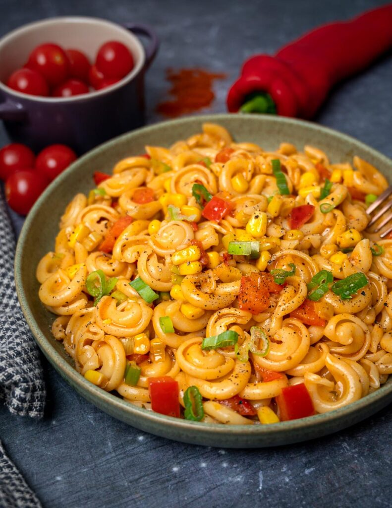 A plate of pasta with peppers and sweetcorn