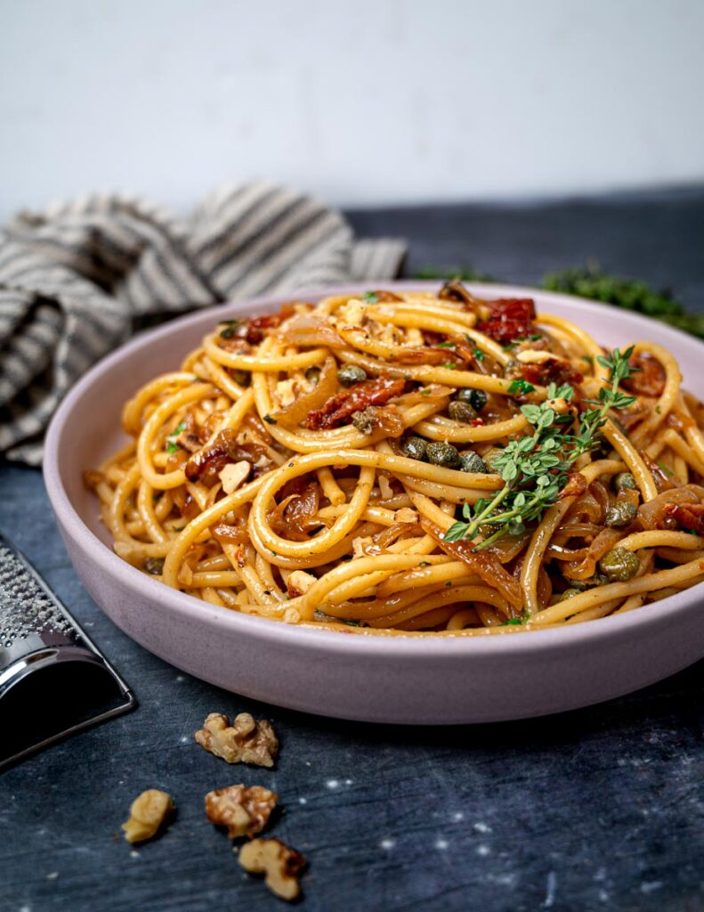 A bowl of vegetarian pasta with sundried tomatoes and capers