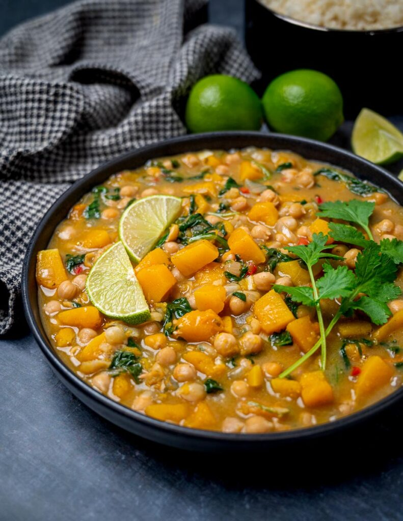 A bowl of vegan curry with lemons on the side