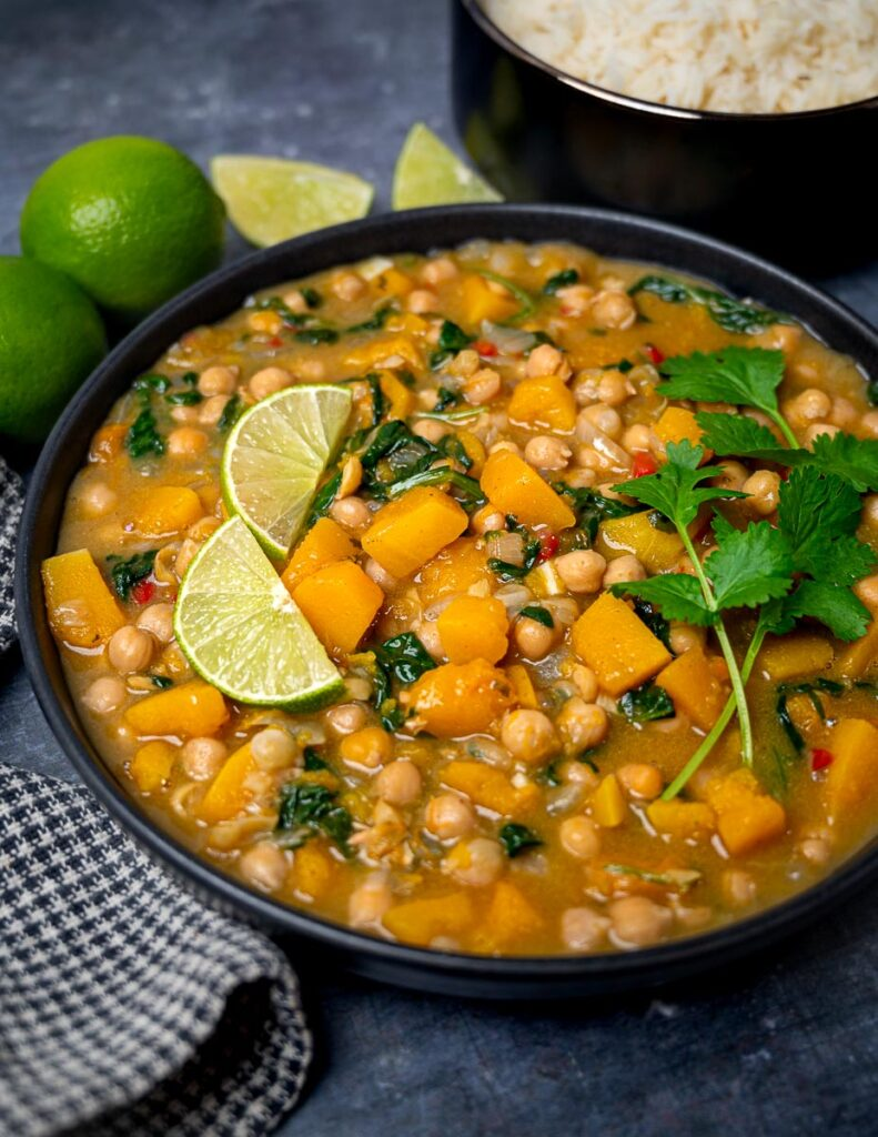 A bowl of butternut squash chickpea curry with lime slices
