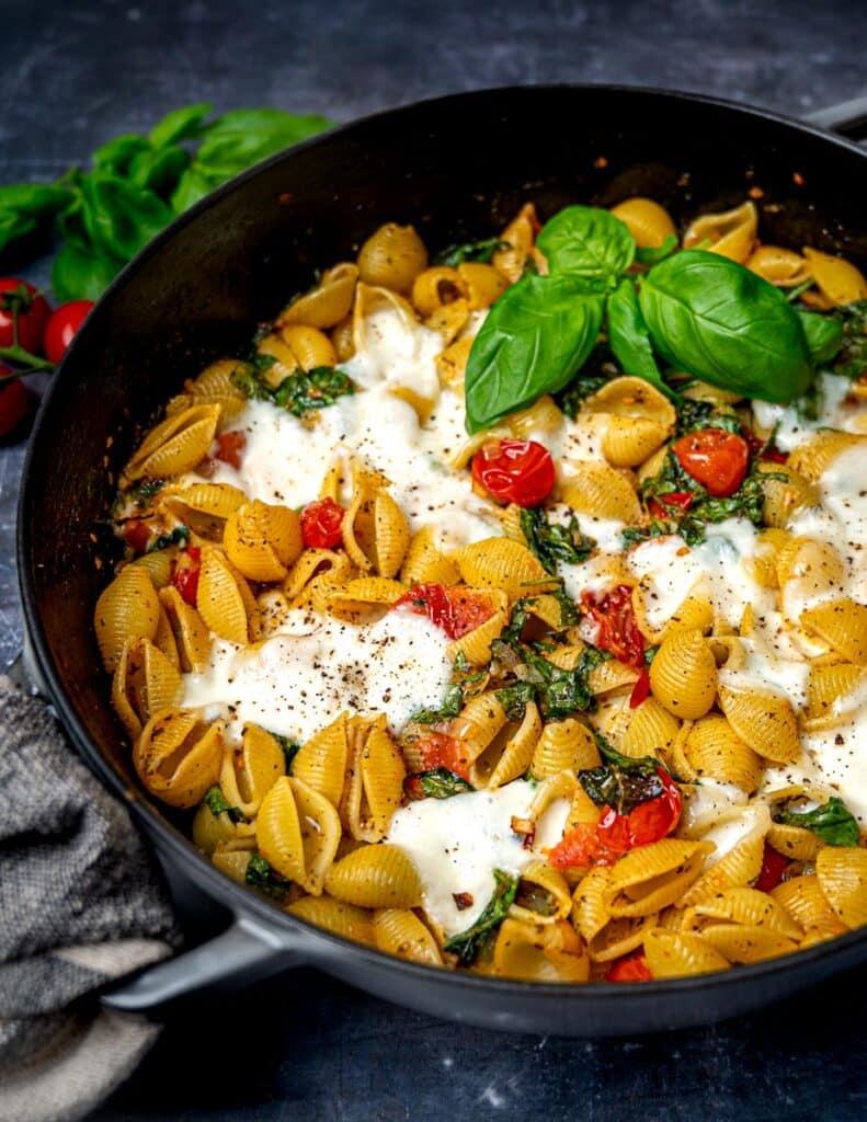 A pan of vegetarian pasta bake with tomatoes, mozzarella and basil