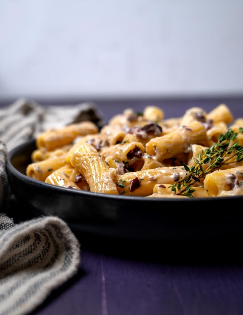 Close up photo of a bowl of pasta with gorgonzola and black olives