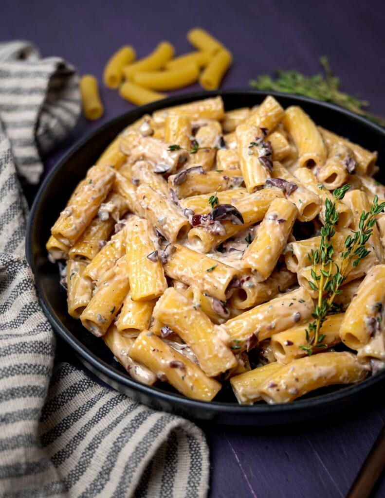 A plate of pasta alla cenere with a sprig of thyme