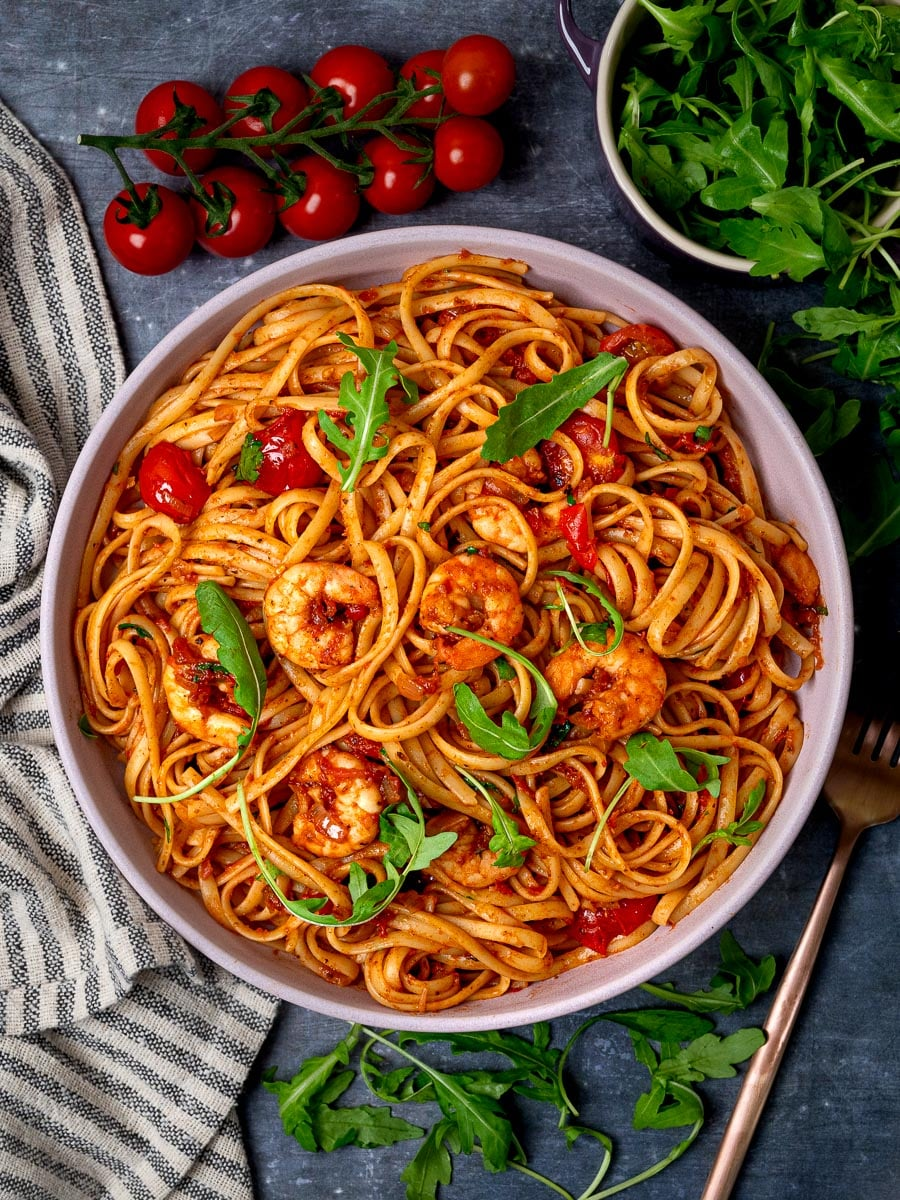 A photo of a pink bowl with spicy prawn pasta